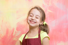 Chef child with happy face. Small girl on colorful background. Childhood and education. Kid in cook apron. Beauty and fashion Stock Photography