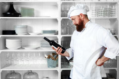 Chef chooses a bottle of wine for guests Stock Image