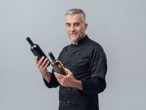 Chef choosing a wine bottle. Professional chef and wine expert comparing wine bottles and reading labels, wine culture concept royalty free stock photo