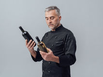 Chef choosing a wine bottle. Professional chef and wine expert comparing wine bottles and reading labels, wine culture concept royalty free stock image