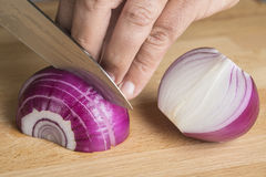 Chef choppig a red onion with a knife Stock Photography