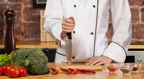 Chef at chopping board. Torso of female chef wearing white jacket holding knife standing next to chopping board with fresh produce and spices royalty free stock image