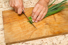 Chef chopping a green onion with a knife on the cutting board Royalty Free Stock Photography