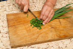 Chef chopping a green onion with a knife on the cutting board Stock Image