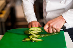 Chef chopping leek over green carving board Royalty Free Stock Photography