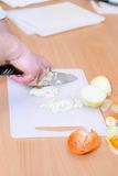 Chef chopping a onion with a knife on the cutting board Stock Photo