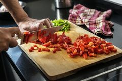Free Chef Chopping Red Pepper On A Wooden Board Royalty Free Stock Image - 114708496