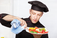 Chef cleaning edge of a fruit plate with cloth Stock Image