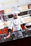 Chef cleaning kitchen. Young male professional chef cleaning in commercial kitchen stock image