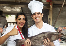 Chef and clerk with fresh fish on a market Stock Image