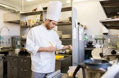 Chef with clipboard doing inventory at kitchen. Cooking, profession and people concept - male chef cook with clipboard doing inventory of restaurant kitchen Royalty Free Stock Photography