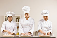 Chef co-workers kneading dough in kitchen Stock Photos