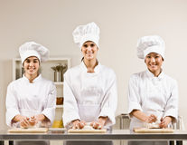 Chef co-workers kneading dough in kitchen Royalty Free Stock Photography