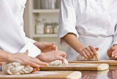 Chef co-workers kneading dough in kitchen