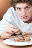 Chef confectioner puts sponge cakes on plate Royalty Free Stock Photography