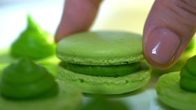 Chef connecting two halves of green pistachio macaroons with cream. Macarons - delicious and beautiful french dessert. Cooking, food and baking, pastry shop stock video footage