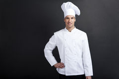Chef cook against dark background smiling with hat holdinf spoon Stock Photo