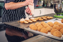 Chef cook baking sweets on a modern kitchen Royalty Free Stock Image
