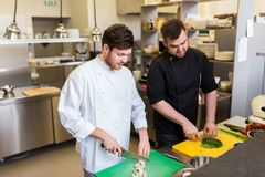 Chef and cook cooking food at restaurant kitchen Stock Photography
