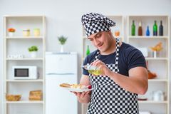 The chef cook cooking a meal breakfast dinner in the kitchen Stock Photo