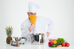Chef cook covering face with pasta Stock Photo