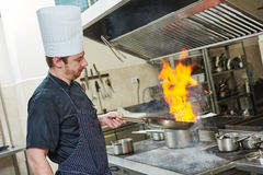 Chef cook doing flambe. Food preparation. Chef cook in restaurant kitchen with pan over stove doing flambe Stock Photo