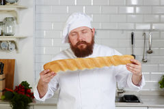 Chef-cook expensive restaurant with pleasure sniffing fresh bread. Portrait of attractive chef-cook smelling beautiful loaf of Italian Bread, young baker with Royalty Free Stock Images