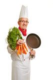Chef cook with frying pan and carrots Stock Photo