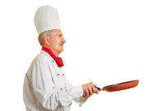 Chef cook holding frying pan while cooking Royalty Free Stock Image