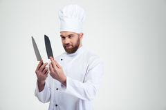 Chef cook holding and looking on knifes Stock Photos