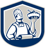 Chef Cook Holding Roller Plate Retro. Illustration of a chef, cook or baker holding up pie pastry with roller in foreground  facing front set inside shield crest Stock Photography