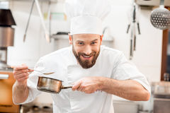Chef cook at the kitchen. Handsome chef cook in uniform tasting sause at the kitchen Stock Photography