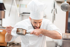 Chef cook at the kitchen. Handsome chef cook in uniform tasting sause at the kitchen Stock Photos
