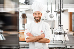 Chef cook at the kitchen. Portrait of handsome positive chef cook at the restaurant kitchen royalty free stock photos