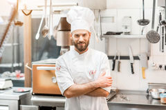 Chef cook at the kitchen. Portrait of chef cook in uniform at the restaurant kitchen stock images