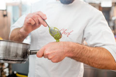 Chef cook at the kitchen. Chef cook putting sause on the hand for tasting Royalty Free Stock Image