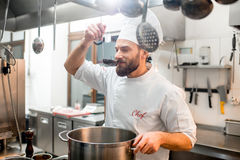 Chef cook at the kitchen. Chef cook tasting food with big scoop at the restaurant kitchen Stock Image