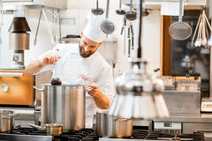 Chef cook at the kitchen. Chef cook in uniform cooking soup in the big cooker at the restaurant kitchen Royalty Free Stock Photo
