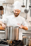 Chef cook at the kitchen. Chef cook in uniform cooking soup in the big cooker at the restaurant kitchen Royalty Free Stock Photos
