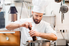 Chef cook at the kitchen. Chef cook in uniform peppering soup in the big cooker at the restaurant kitchen Stock Photos