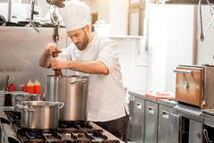 Chef cook at the kitchen. Chef cook in uniform peppering soup in the big cooker at the restaurant kitchen Royalty Free Stock Images