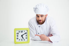 Chef cook leaning on the table with clock Stock Images