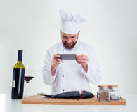 Chef cook making photo of fish on cutting board Stock Images