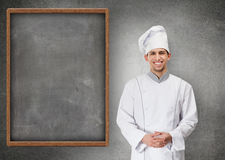 Chef cook near menu blackboard. Portrait of smiling chef cook standing near grey menu blackboard, isolated on grey Royalty Free Stock Photos