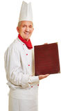 Chef cook offering menu. Smiling chef cook in workwear offering menu royalty free stock image
