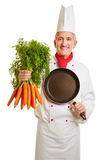 Chef cook with pan and bunch of carrots. Happy chef cook in workwear with a pan and bunch of carrots Stock Images