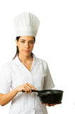 Isolated Chef Cooking. Vertical photo of a beautiful smiling cook, holding a black pot and a black heat resistant ladle. Isolated on white background. She is Stock Photo