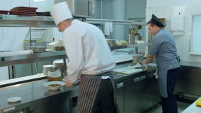 Chef and cook pouring sauces for prepared dish stock footage