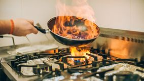 Chef cook prepares meal in flame fire burn frying pan. Chef cook prepares a meal in the frying pan with flame fire burn in the kitchen in the restaurant stock images