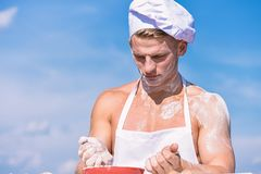 Chef cook preparing dough for baking. Cook or chef with muscular shoulders and chest mixing flour in bowl. Cookery. Concept. Man on confident face wears cooking royalty free stock photo